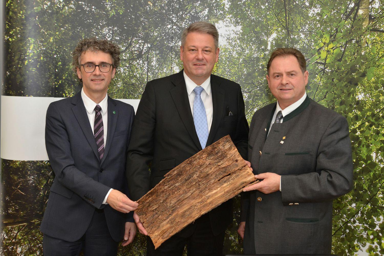 links nach rechts: Peter Mayer, Bundesminister Andrä Rupprechter und Rudi Rosenstatter mit von <span class='term-desc-marker' alt='Borkenkäfer'>Borkenkäfer</span>n gezeichneten Baumrinde.