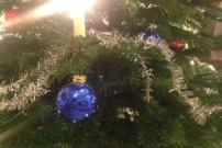 Blaue Christbaumkugel auf Tannenbaum und weiterer Schmuck